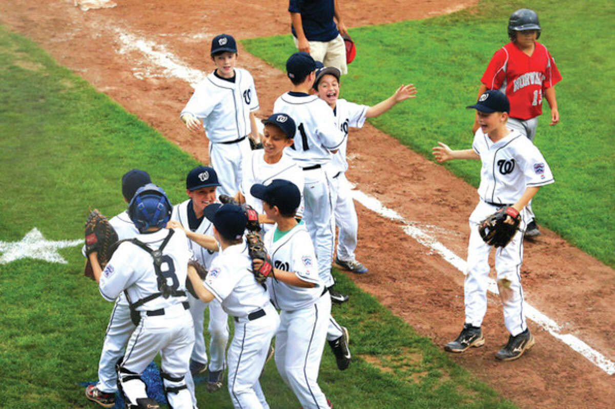 Hour photo/Chris Palermo Wilton players begin to celebrate after capturing the 10-year-old District 1 Little League championship Friday with a 5-1 victory over Norwalk at the Springdale Little League Field.