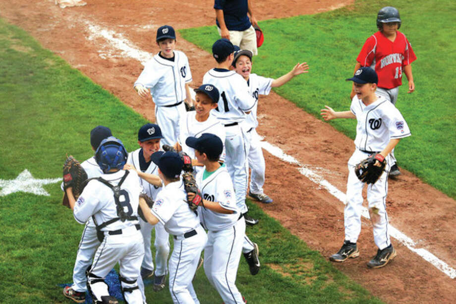 Hour photo/Chris PalermoWilton players begin to celebrate after capturing the 10-year-old District 1 Little League championship Friday with a 5-1 victory over Norwalk at the Springdale Little League Field. / © 2013 Hour Newspapers All Rights Reserved