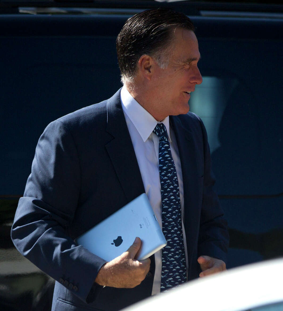 Republican presidential candidate, former Massachusetts Gov. Mitt Romney, carries an iPad as he walks into the Church of Jesus Christ of Latter-day Saints on Sunday, Aug. 19, 2012, in Wolfeboro, N.H. (AP Photo/Evan Vucci)