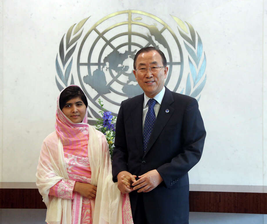 """United Nations Secretary-General Ban Ki-moon, right, holds Malala Yousafzai's hand while posing for photographers, Friday, July 12, 2013 at United Nations headquarters. Malala Yousafzai, the Pakistani teenager shot by the Taliban for promoting education for girls, celebrated her 16th birthday on Friday addressing the United Nations. The U.N. has declared July 12 """"Malala Day,"""" to honor the teen who returned to school in March after medical treatment in Britain for injuries suffered in the October attack. (AP Photo/Mary Altaffer) / AP"""