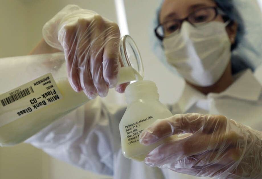 In this photo taken Thursday, Aug. 16, 2012, Kelly Fischl, a lab technician at the Mothers' Milk Bank of New England in Newtonville, Mass., pours donated breast milk into a plastic bottle for pasteurization. The pathogens are removed so the milk can be distributed to babies in need. Now a year into operation, officials at Mothers' Milk Bank of New England said it's the only facility of its sort in the region and one of only a dozen similar operations in North America. (AP Photo/Elise Amendola) / AP