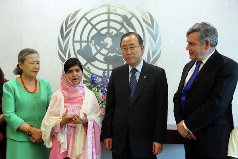 """Malala Yousafzai, second from left, speaks to reporters while posing for a photo with United Nations Secretary-General Ban Ki-moon, second from right, his wife Ban Soon-taek, left, and former British Prime Minister Gordon Brown, Friday, July 12, 2013 at United Nations headquarters. Malala Yousafzai, the Pakistani teenager shot by the Taliban for promoting education for girls, celebrated her 16th birthday on Friday by addressing the United Nations. The U.N. has declared July 12 """"Malala Day,"""" to honor the teen who returned to school in March after medical treatment in Britain for injuries suffered in the October attack. (AP Photo/Mary Altaffer) / AP"""