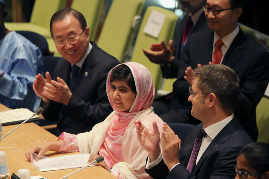 """United Nations Secretary-General Ban Ki-moon, left, applauds as the members of the 'Malala Day' Youth Assembly wish Malala Yousafzai, center, a happy birthday, Friday, July 12, 2013 at United Nations headquarters. Yousafzai, the Pakistani teenager shot by the Taliban for promoting education for girls, celebrated her 16th birthday on Friday by addressing the United Nations. The U.N. has declared July 12 """"Malala Day,"""" to honor the teen who returned to school in March after medical treatment in Britain for injuries suffered in the October attack. (AP Photo/Mary Altaffer) / AP"""