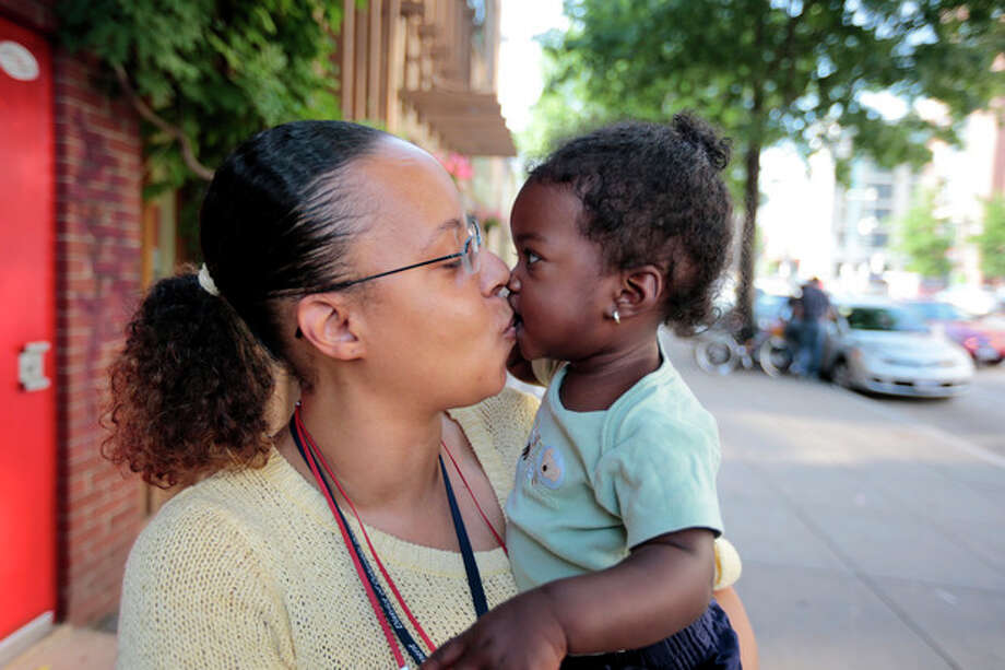 Ke'sha Scrivner, left, kisses her daughter as they pose for a photograph after picking up her daughter Ka'Lani Scrivner, 1, from day care, Tuesday, July 9, 2013, in Washington. Once on welfare, Scrivner worked her way off by studying early childhood education and landing a full-time job for the District of Columbia's education superintendent. She sees education as the path to a better life for herself and all five of her children, pushing them to finish high school and continue with college or a trade school. (AP Photo/Alex Brandon) / AP