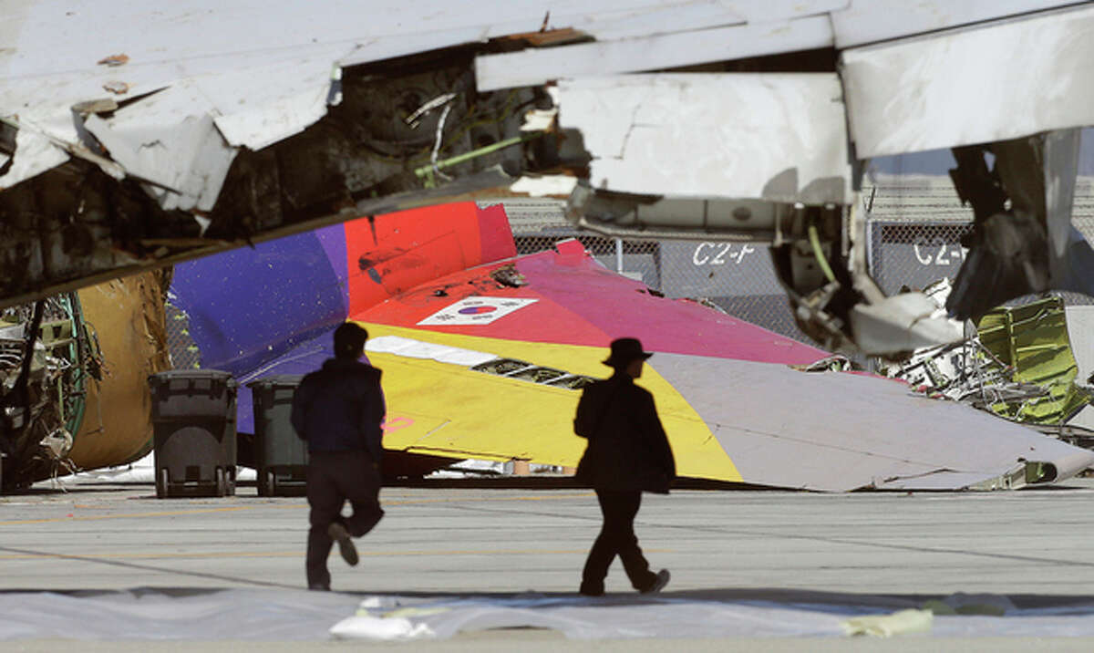 A South Korean flag is seen on the tail of Asiana Flight 214, which crashed on Saturday, July 6, 2013, as two men walk under a wing at San Francisco International Airport, in San Francisco, Friday, July 12, 2013. Two people were killed and dozens of others injured although most suffered minor injuries. Investigators have said the plane came in too low and slow. (AP Photo/Jeff Chiu)