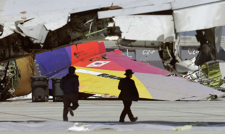 A South Korean flag is seen on the tail of Asiana Flight 214, which crashed on Saturday, July 6, 2013, as two men walk under a wing at San Francisco International Airport, in San Francisco, Friday, July 12, 2013. Two people were killed and dozens of others injured although most suffered minor injuries. Investigators have said the plane came in too low and slow. (AP Photo/Jeff Chiu) / AP