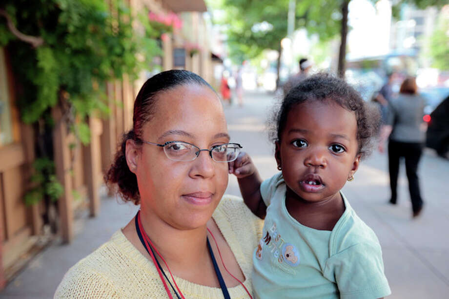 Ke'sha Scrivner, left, poses for a photograph after picking up her daughter Ka'Lani Scrivner, 1, from day care, Tuesday, July 9, 2013, in Washington. Once on welfare, Scrivner worked her way off by studying early childhood education and landing a full-time job for the District of Columbia's education superintendent. She sees education as the path to a better life for herself and all five of her children, pushing them to finish high school and continue with college or a trade school. (AP Photo/Alex Brandon) / AP