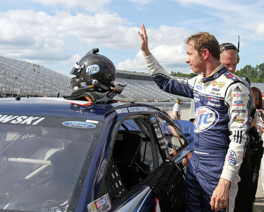 Brad Keselowski waves to a few cheering fans in the stands after winning the pole during qualifying for the NASCAR Sprint Cup auto race on Friday, July 12, 2013, in Loudon, N.H. (AP Photo/Mary Schwalm) / FR158029 AP