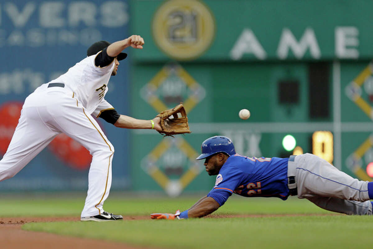 Pittsburgh Pirates shortstop Jordy Mercer waits for the throw from catcher Russell Martin before putting the tag on New York Mets' Eric Young Jr. (22), who attempted to steal second during the first inning of a baseball game in Pittsburgh on Friday, July 12, 2013. (AP Photo/Gene J. Puskar)