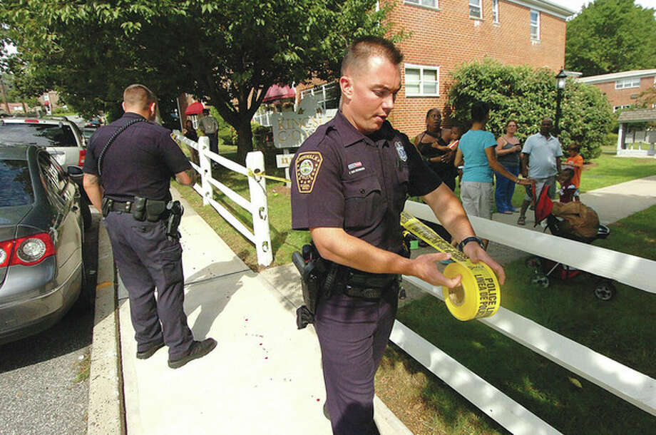 Hour photo/ Alex von KleydorffNorwalk Police tape off a sidewalk on Bedford Avenue to protect blood drops left from a stabbing victim Monday morning. / 2012 The Hour Newspapers