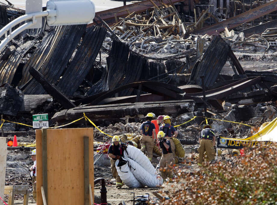 Crews work on the aftermath of the Lac-Megantic, Quebec, oil train derailment wreck on Friday, July 12, 2013. The bodies of less than half of the 50 people believed dead in a runaway oil train's explosive derailment have been recovered, nearly a week after the accident which demolished a large part of the Quebec town. (AP Photo/The Canadian Press, Ryan Remiorz)
