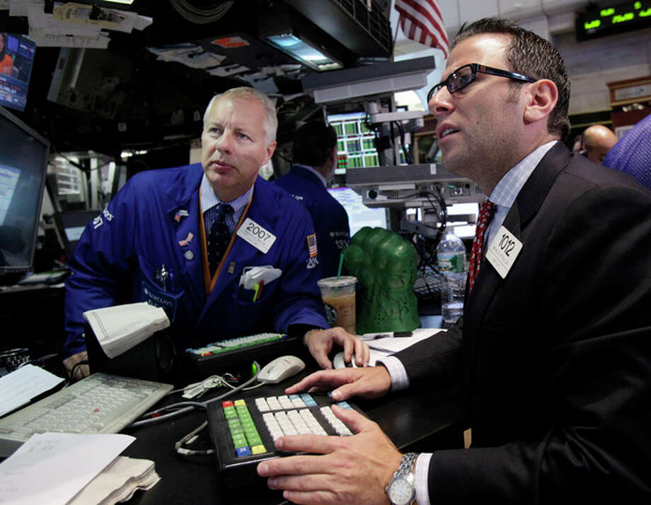 FILE - In this Aug. 15, 2012 file photo, specialists Thomas Bishop, left, and Michael Pistillo work at their post on the floor of the New York Stock Exchange. Stocks are ending the Monday, just lower as Apple became the most valuable company ever, with a market value of $623 billion, surpassing Microsoft's record from 1999. (AP Photo/Richard Drew, File) / AP