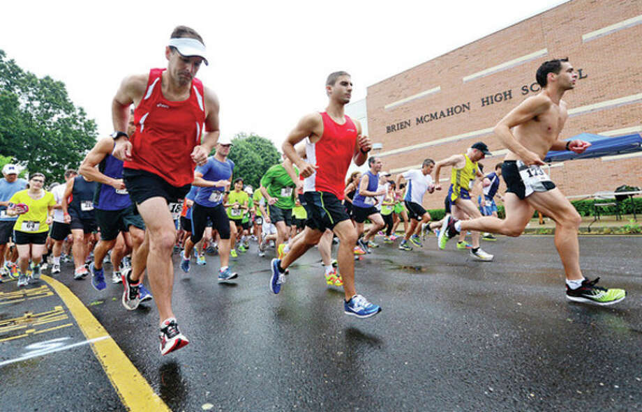 Hour photo/Erik TrautmannRunners head out from the starting line of Saturday's Lightfoot Running Club's Norwalk Running Series 7-mile road race outside of Brien McMahon High School in Norwalk. / (C)2013, The Hour Newspapers, all rights reserved