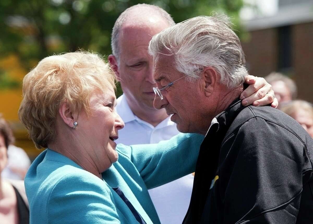 FILE- In this July 11, 2013, file photo, Raymond Lafontaine, who lost his son and two daughters-in-law, receives a hug from Quebec Premier Pauline Marois during her visit to Lac-Megantic, Quebec as Marois toured the site where a runaway oil train killed 50 people in a fiery explosion. (AP Photo/The Canadian Press, Ryan Remiorz, File)