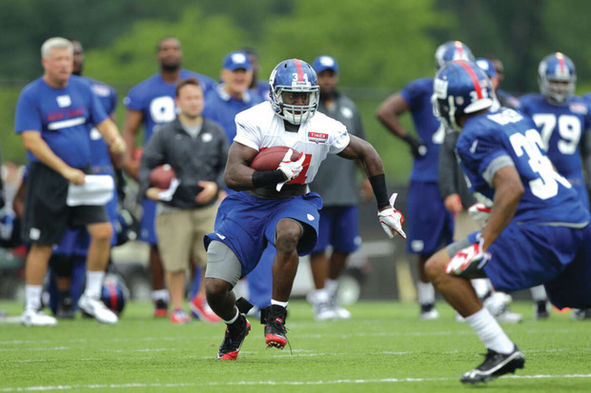 AP photo New York Giants running back and 2012 first round draft pick David Wilson, left, runs with the ball as cornerback Jayron Hosley defends during a training camp session in Albany, N.Y. Wilson is expected get see action Friday night against the Chicago Bears.