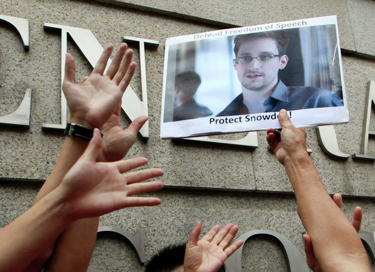 A supporter holds a picture of Edward Snowden, a former CIA employee who leaked top-secret information about U.S. surveillance programs, outside the U.S. Consulate General in Hong Kong Thursday, June 13, 2013. The news of Snowden's whereabouts, revealed by an editor of a local newspaper that interviewed him Wednesday, is the first since he went to ground Monday after checking out of his hotel in this autonomous Chinese territory. (AP Photo/Kin Cheung)