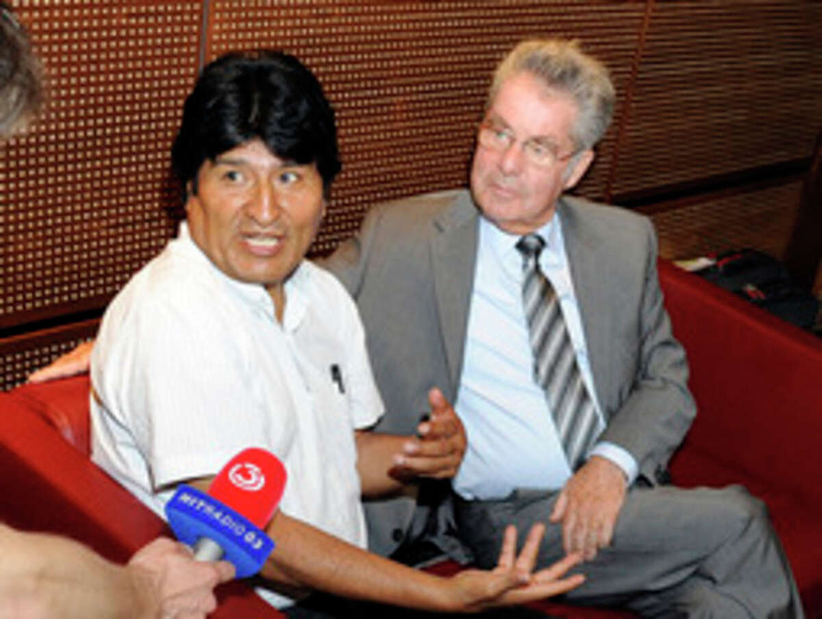 Bolivia's President Evo Morales, left, talks to reporters as he sits next to Austrian President Heinz Fischer at Vienna's Schwechat airport, Wednesday, July 3, 2013. The plane of Morales was rerouted to Austria after various European countries refused to let it cross their airspace because of suspicions that NSA leaker Edward Snowden was on board, Bolivian officials said Tuesday. Officials in both Austria and Bolivia said that Snowden was not on the plane, which was taking Morales home from a summit in Russia, where he had suggested that his government would be willing to consider granting asylum to the American. (AP Photo/Hans Punz)