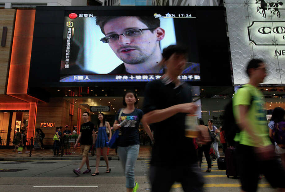 FILE - This June 23, 2013 file photo shows a TV screen shows a news report of Edward Snowden, a former CIA employee who leaked top-secret documents about sweeping U.S. surveillance programs, at a shopping mall in Hong Kong. The saga of Edward Snowden and the NSA makes one thing clear: The United States' central role in developing the Internet and hosting its most powerful players has made it the global leader in the surveillance game . Other countries, from dictatorships to democracies, are also avid snoopers, tapping into the high-capacity fiber optic cables to intercept Internet traffic, scooping their citizens' data off domestic servers, and even launching cyberattacks to win access to foreign networks. (AP Photo/Vincent Yu, File) / AP