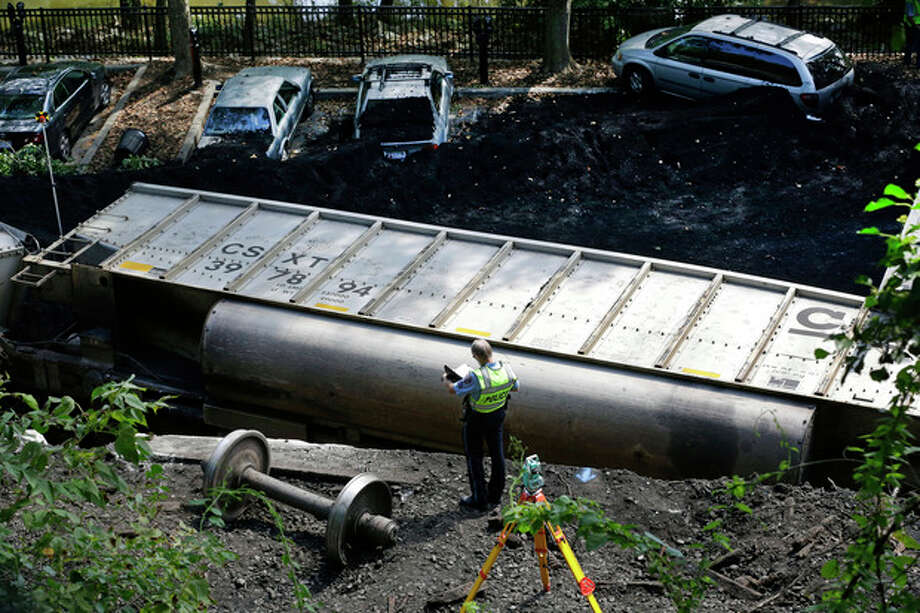 An official inspects part of a CSX freight train that derailed alongside a parking lot overnight in Ellicott City, Md., Tuesday, Aug. 21, 2012. Authorities said two people not employed by the railroad were killed in the incident. The victims were Elizabeth Conway Nass, a student at James Madison University in Virginia, and Rose Louese Mayr, who attended the University of Delaware, according to Howard County police spokeswoman Sherry Llewellyn. They were both 19 years old. Police did not immediately say what the women were doing on the tracks. (AP Photo/Patrick Semansky) / AP