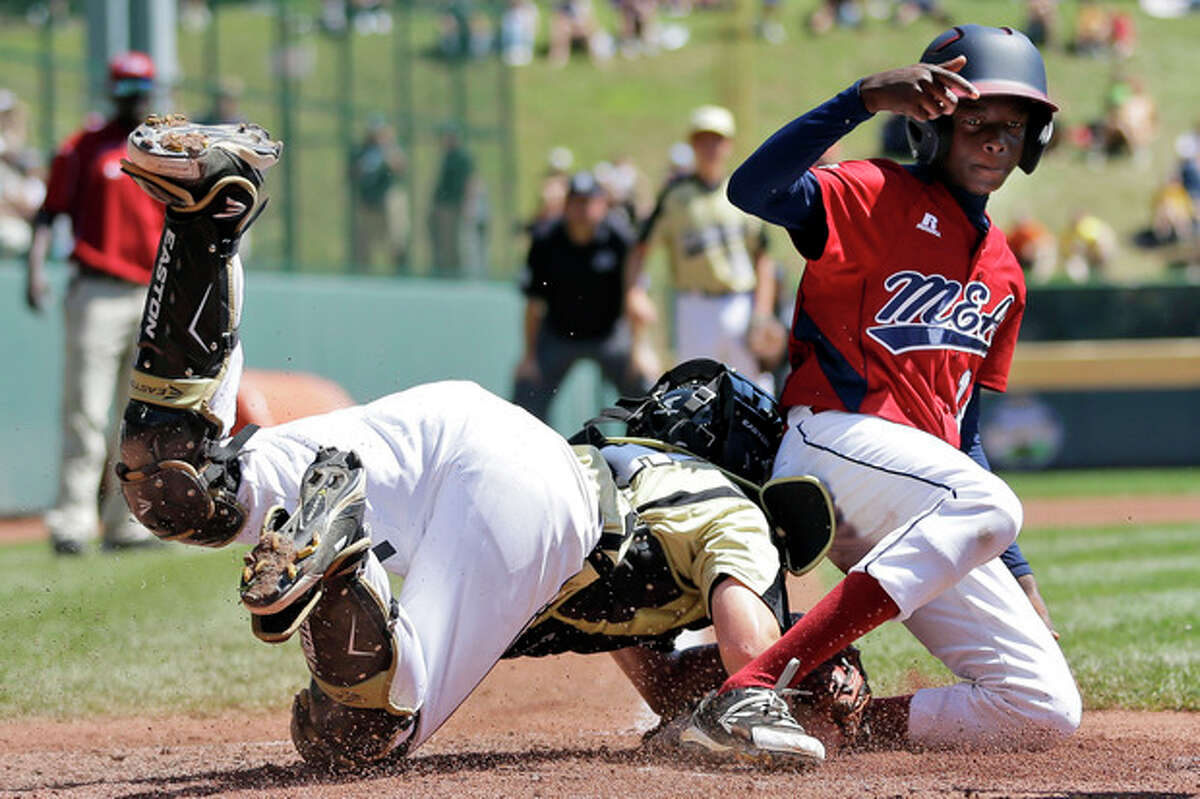 Lugazi, Uganda's Daniel Alio, right, scores past Gresham, Ore.'s Tyler Pederson on a wild pitch in the fourth inning of a consolation baseball game at the Little League World Series, Tuesday, Aug. 21, 2012, in South Williamsport, Pa. Uganda won 3-2. (AP Photo/Matt Slocum)