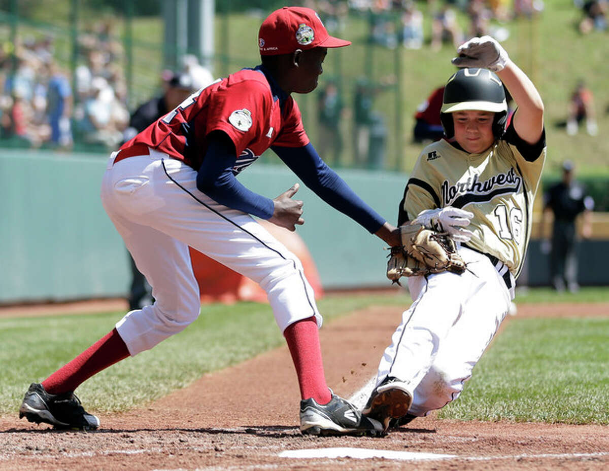 Lugazi, Uganda's Daniel Alio, left, tags out Gresham, Ore.'s Hunter Hemenway after Hemenway tried to score on a wild pitch in the fourth inning of a consolation baseball game at the Little League World Series, Tuesday, Aug. 21, 2012, in South Williamsport, Pa. Uganda won 3-2. (AP Photo/Matt Slocum)