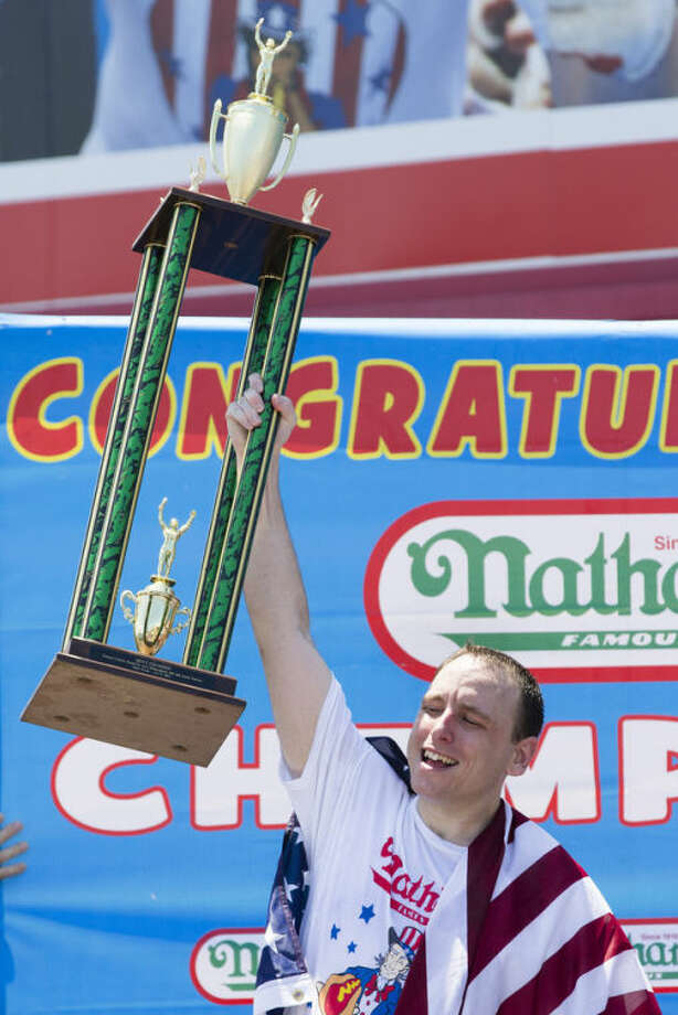 Joey Chestnut celebrates after winning the Nathan's Famous Fourth of July International Hot Dog Eating contest with a total of 69 hot dogs and buns, Thursday, July 4, 2013 at Coney Island, in the Brooklyn borough of New York. (AP Photo/John Minchillo)
