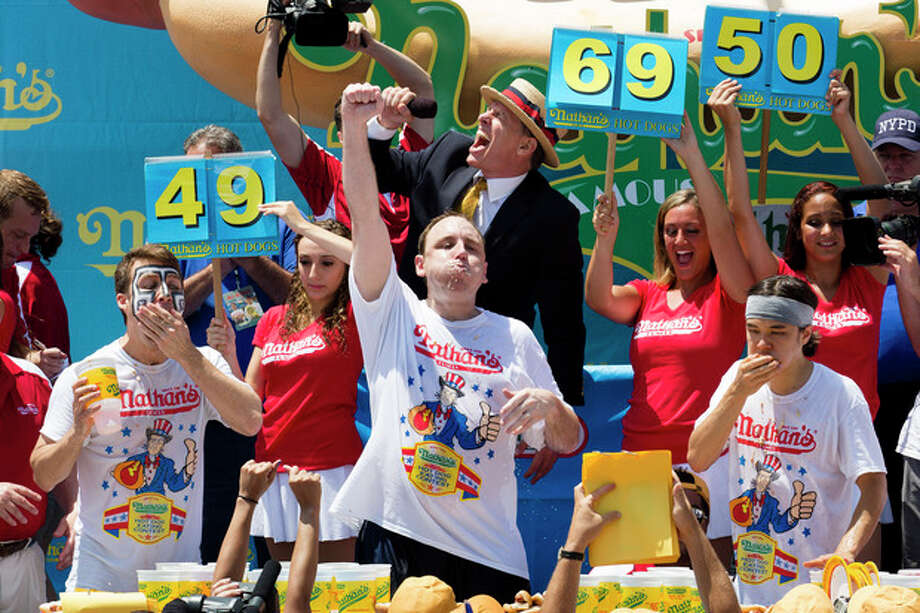 Joey Chestnut, center, wins the Nathan's Famous Fourth of July International Hot Dog Eating contest with a total of 69 hot dogs and buns, alongside Tim Janus, left, and Matt Stonie, right, Thursday, July 4, 2013 at Coney Island, in the Brooklyn borough of New York. (AP Photo/John Minchillo) / FR170537 AP