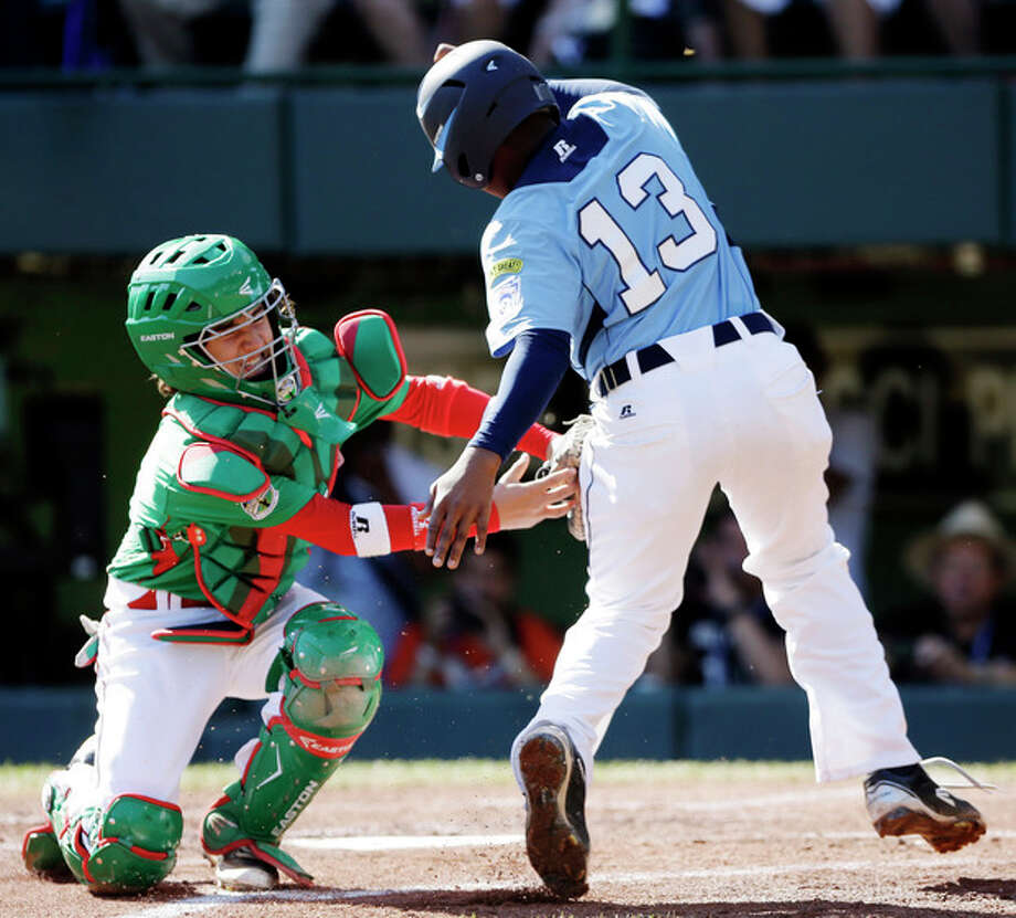 Willemstad, Curacao's Christopher Koeiman, right, is tagged out at home by Nuevo Laredo, Mexico catcher Eduardo Abrego while trying to score on a ground out by Railison Bentura in the first inning of a baseball game at the Little League World Series, Tuesday, Aug. 21, 2012, in South Williamsport, Pa. Mexico won 6-2. (AP Photo/Matt Slocum) / AP