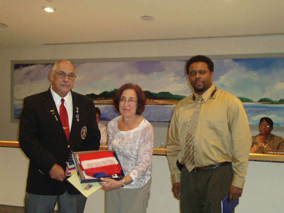 Dr. Susan Marks holds the American flag presented to her by Norwalk Veterans Memorial Committee Chairman Dan Caporale (left) and Jarvin Johnson, veterans affairs specialist for Congressman Jim Himes, D-4.