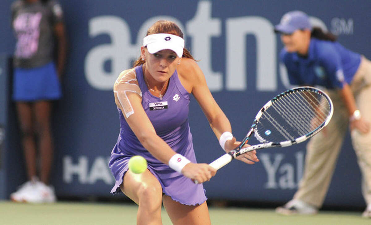 Hour photo/John Nash Top-seeded Agnieszka Radwanska of Poland, with her right shoulder heavily taped, looks to hit a return during her second round match at the New Haven Open at Yale on Tuesday. When Radwanska was forced to retire, trailing 6-0, 2-1, it became the earliest exit for a top-seed in the tournament's 15-year-history.