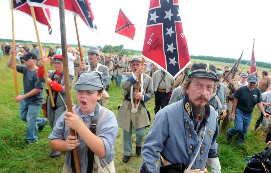 Paul Karabin, right, portraying Maj. Gen. George Pickett and Brodee Daniel, portraying Pickett's flag holder, participate in the Pickett's Charge commemorative march on Wednesday, July 3, 2013 during ongoing activities commemorating the 150th anniversary of the Battle of Gettysburg, Wednesday, July 3, 2013, in Gettysburg, Pa. (AP Photo/York Daily Record, Jason Plotkin) / York Daily Record/Sunday News