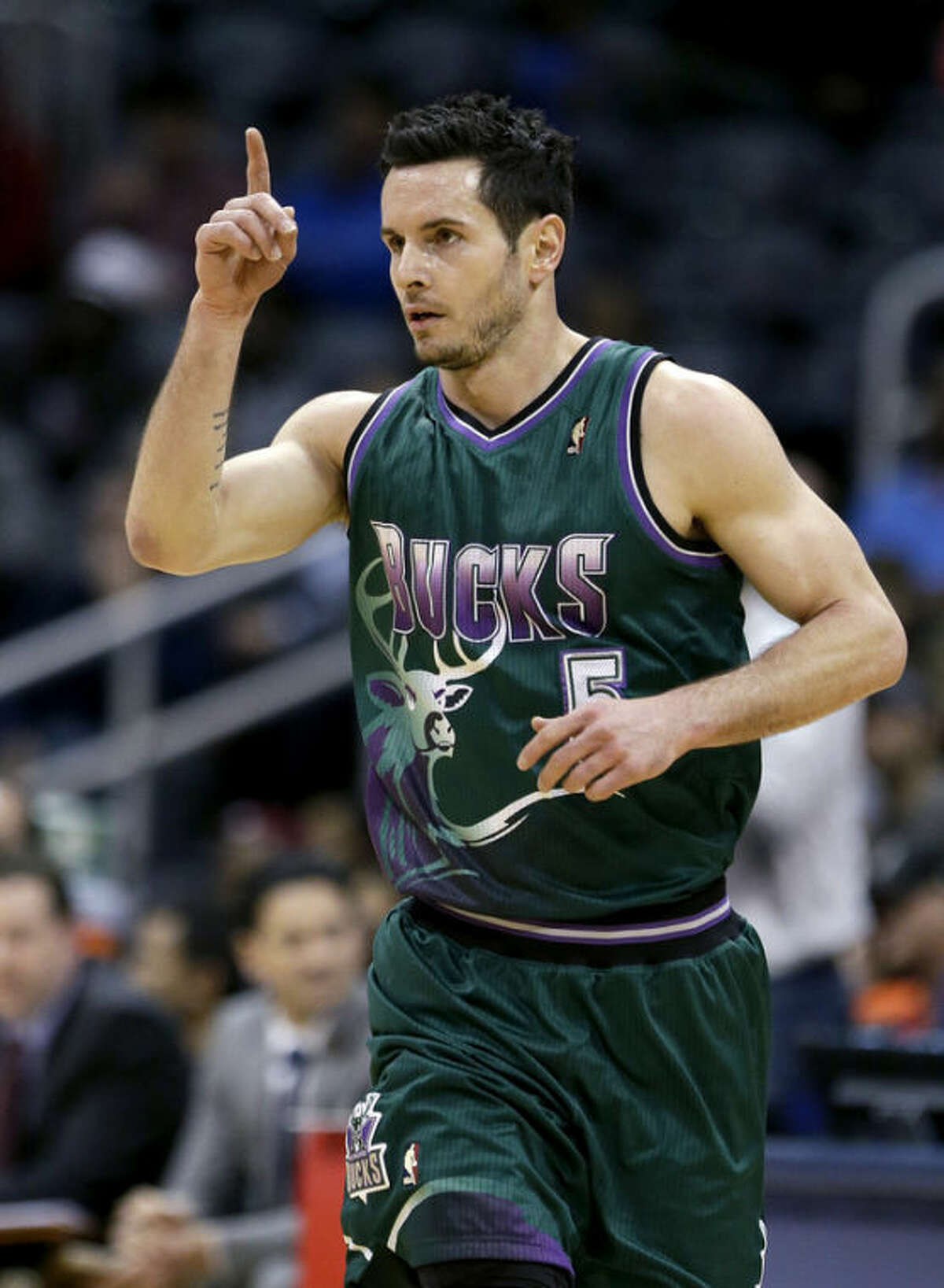 In this March 20, 2013, photo, Milwaukee Bucks guard J.J. Redick gestures during an NBA basketball game against the Atlanta Hawks in Atlanta. A person with knowledge of the situation says a three-team trade is in place that sends Redick from the Bucks to the Los Angeles Clippers and point guard Eric Bledsoe from the Clippers to the Phoenix Suns. The deal also sends Jared Dudley from the Suns to the Clippers and Caron Butler from the Clippers to the Suns. (AP Photo/David Goldman)
