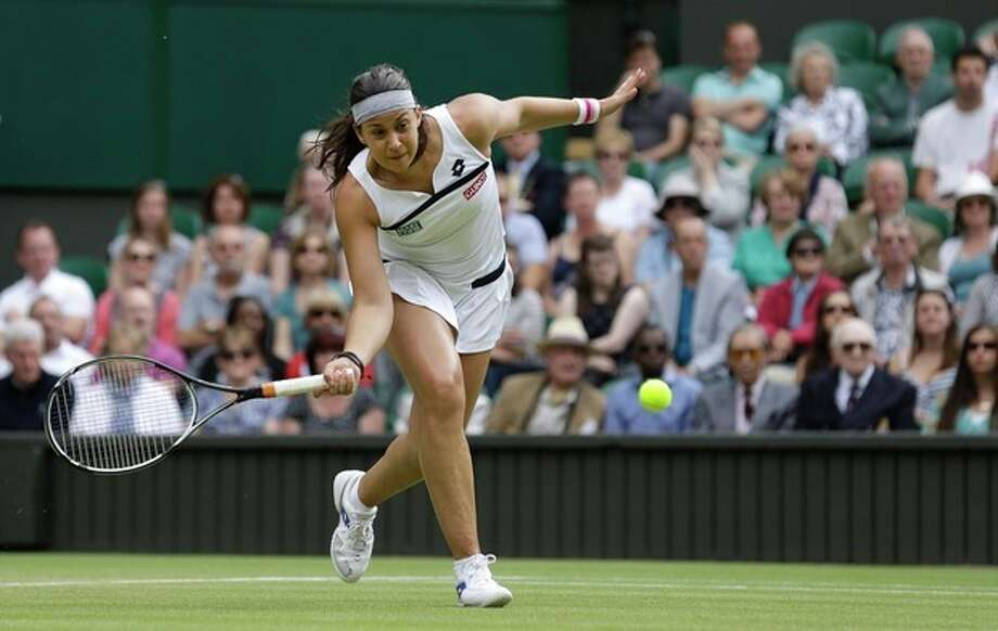 Marion Bartoli of France plays a return to Kirsten Flipkens of Belgium in a Women's singles semifinal match at the All England Lawn Tennis Championships in Wimbledon, London, Thursday, July 4, 2013. (AP Photo/Anja Niedringhaus) / AP