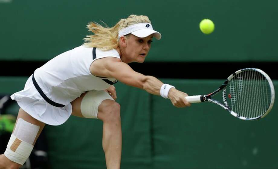 Agnieszka Radwanska of Poland plays a return to Sabine Lisicki of Germany during their Women's singles semifinal match at the All England Lawn Tennis Championships in Wimbledon, London, Thursday, July 4, 2013. (AP Photo/Anja Niedringhaus) / AP