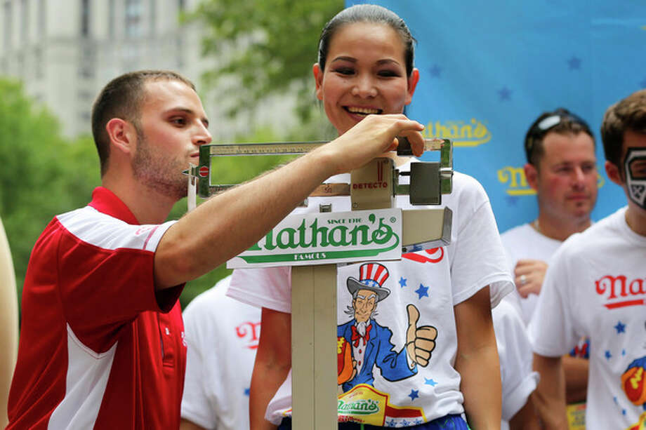 Sonya Thomas smiles as she stands on the scale during the official weigh-in for the Nathan's Fourth of July hot dog eating contest, Wednesday, July 3, 2013 at City Hall park in New York. (AP Photo/Mary Altaffer) / AP