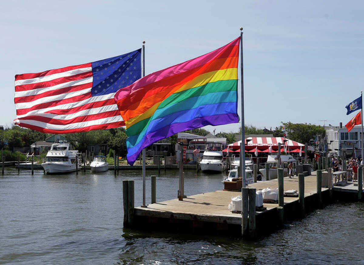 AP Photo/Seth Wenig In this June 23, photo, an American flag and a LGBT Rainbow flag are displayed on the ferry dock in the Fire Island community of Cherry Grove, N.Y.