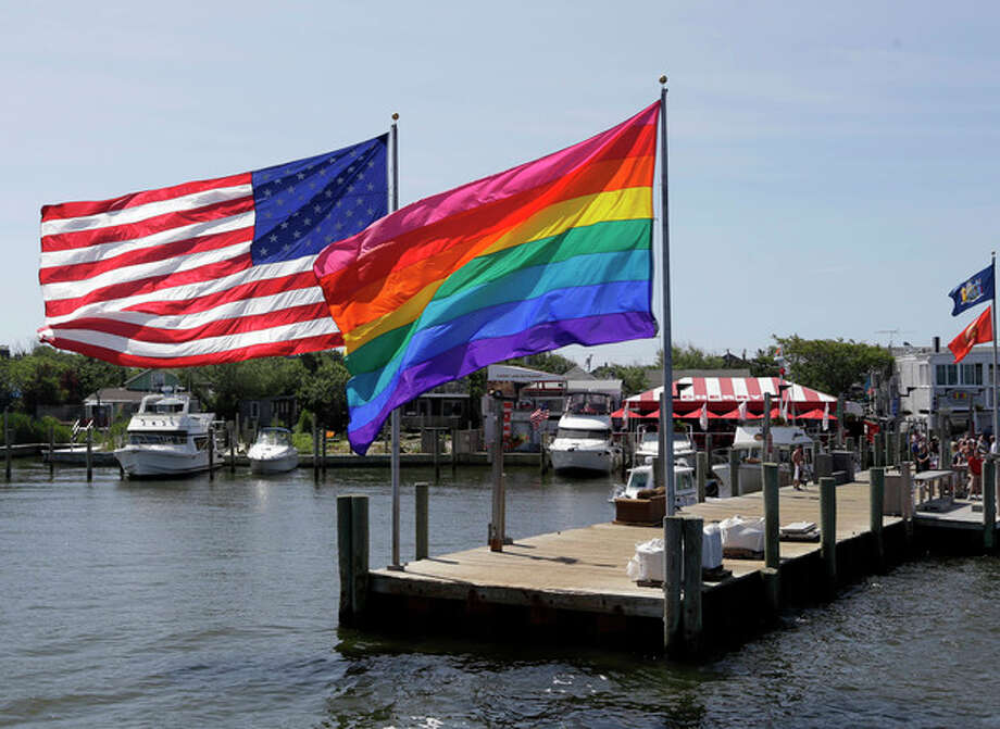 AP Photo/Seth WenigIn this June 23, photo, an American flag and a LGBT Rainbow flag are displayed on the ferry dock in the Fire Island community of Cherry Grove, N.Y. / AP
