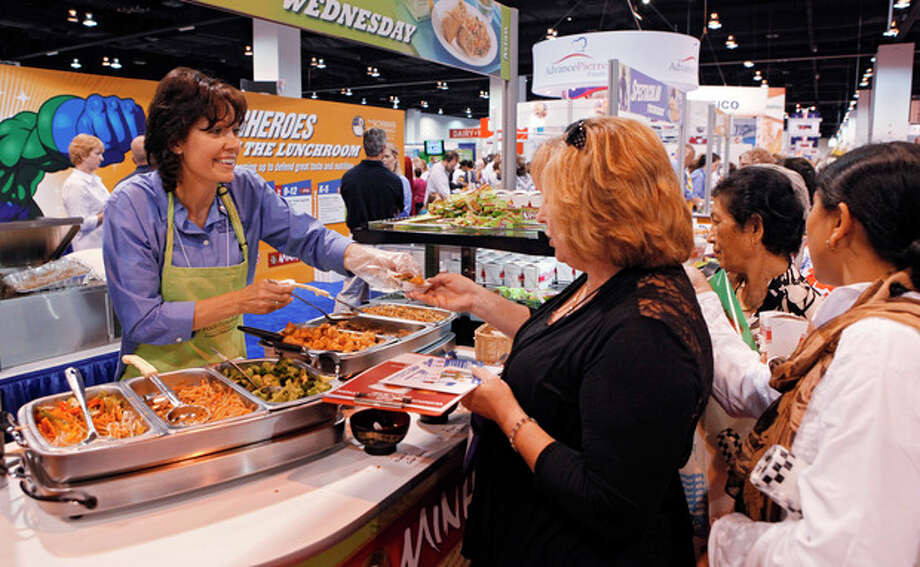 In this July 17, 2012 photo Diane Wagner, with Schwan Food Co., hands out samples of food at a booth during the School Nutrition Association conference in Denver. There are plenty of vegetables and other healthy options on school menus these days. The challenge is getting children to eat them. (AP Photo/Ed Andrieski) / AP
