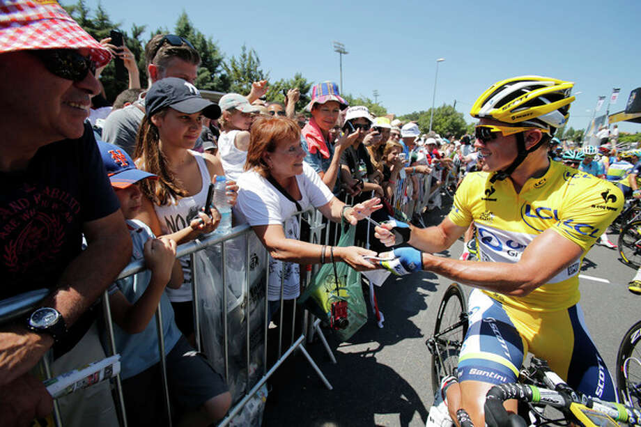 Simon Gerrans of Australia, wearing the overall leader's yellow jersey, signs autographs as he waits for the start of the sixth stage of the Tour de France cycling race over 176.5 kilometers (110.3 miles) with start in Aix-en-Provence and finish in Montpellier, southern France, Thursday July 4, 2013. (AP Photo/Christophe Ena) / AP