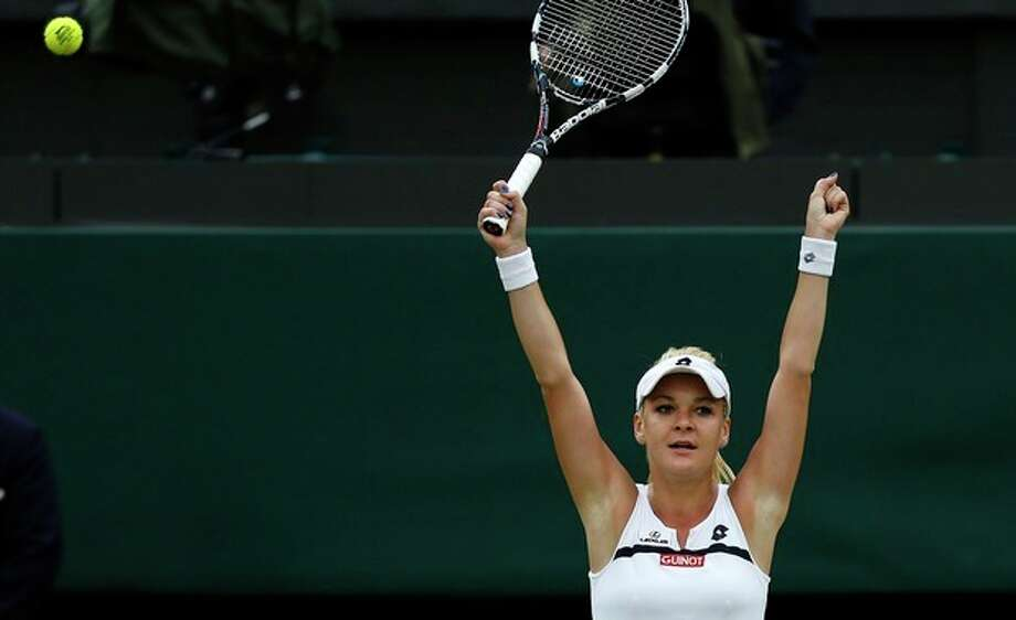 Agnieszka Radwanska of Poland reacts as she defeats Li Na of China in their Women's singles quarterfinal match at the All England Lawn Tennis Championships in Wimbledon, London, Tuesday, July 2, 2013. (AP Photo/Sang Tan) / AP