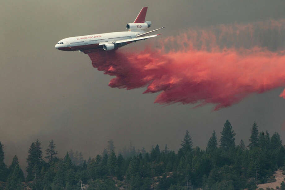 A DC-10 drops fire retardant on the Ponderosa Fire Monday Aug. 20, 2012, near Paynes Creek, Calif. Nearly 1,900 firefighters were battling the Ponderosa Fire in rugged, densely forested terrain as it threatened 3,500 homes in the towns of Manton, Shingletown and Viola, about 170 miles north of Sacramento. (AP Photo/The Record Searchlight, Andreas Fuhrmann) / The Record Searchlight