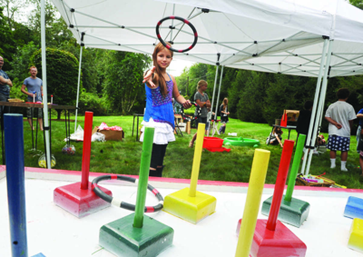 Sadie Kinnersley, 9, plays the ring toss Sunday at the Cannon Grange 80th annual agricultural fair in Wilton.