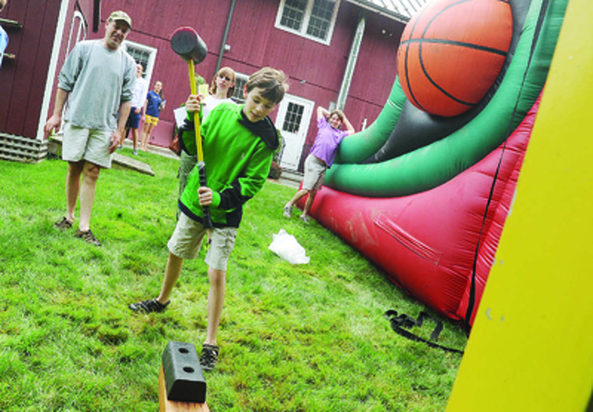 Kyle Rubin 13, does the test of strength game Sunday at the Cannon Grange 80th annual agricultural fair in Wilton.