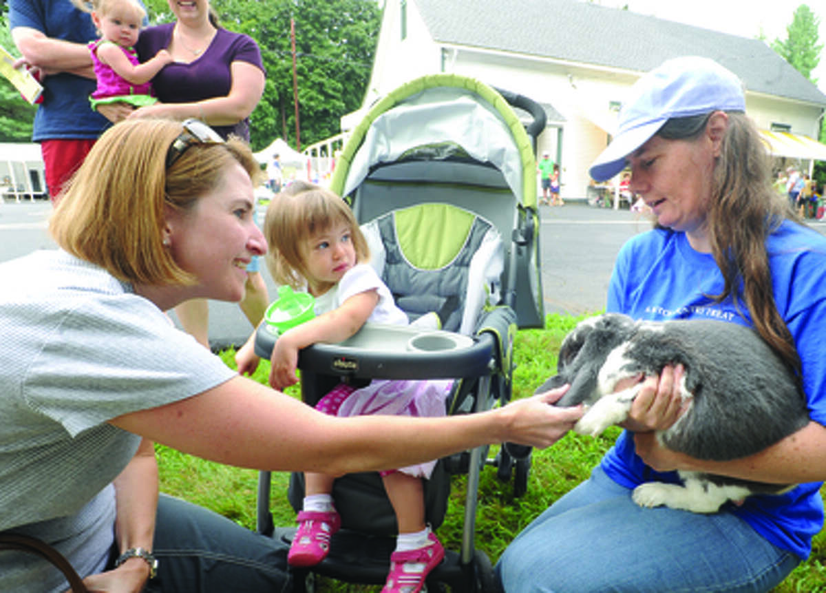 Tessa Simpson with her mother, Jen, has never seen a such a large rabbit that Wendy Griffin holds which is an English Lop rabbit at the Cannon Grange 80th annual agricultural fair in Wilton.