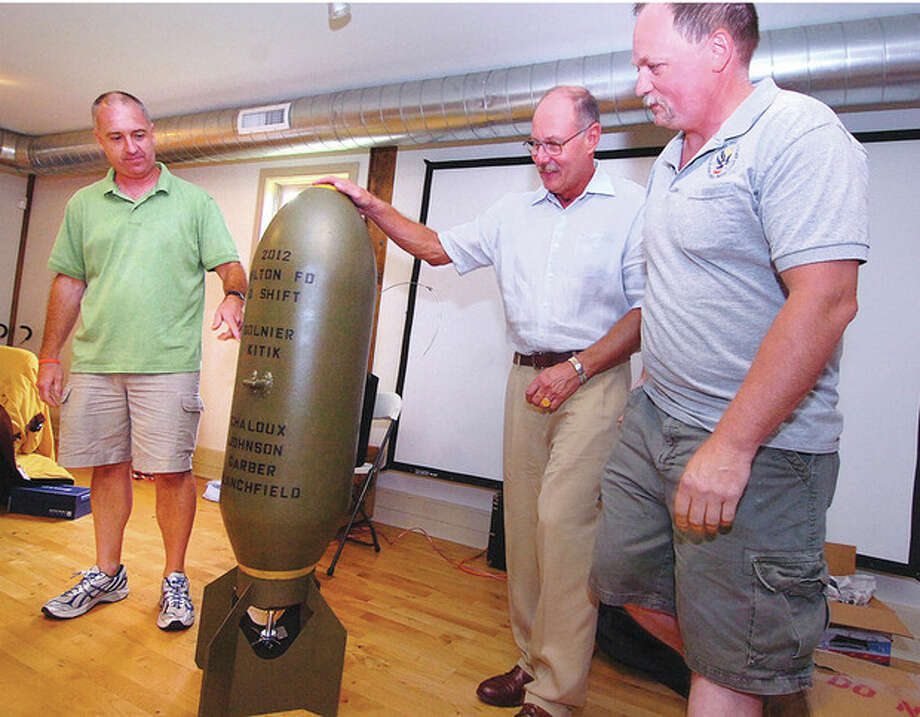 Hour Photo/ Alex von Kleydorff. Firefighter Pat Garber and Lt. Gregg Kitik on behalf of 'D shift' present Capt Karl Dolnier a surplus bomb at his retirement party on Sunday at Wilton's Ambler farm / 2012 The Hour Newspapers