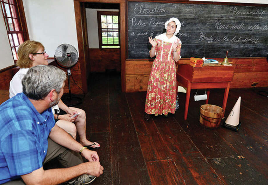 Hour photo/Erik TrautmannAbove, educational coordinator Samantha Kulish gives tours of the old schoolhouse during the Norwalk Historical Society's Independence Day celebration at the Mill Hill complex Thursday. At right, Edward and Madeleine Eckert gives a historical tour of the Norwalk Town Green. / (C)2013, The Hour Newspapers, all rights reserved
