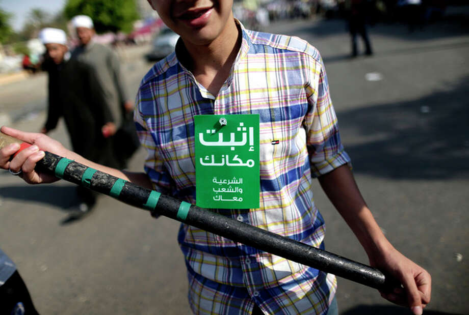 """A supporter of Egypt's Islamist President Mohammed Morsi holds a stick during a rally, in Nasser City, Cairo, Egypt, Wednesday, July 3, 2013. Arabic on the green card reads, """"stay where you are, the shariya (legitimacy) and the people are with you."""" Egypt's military moved to tighten its control on key institutions Wednesday, even putting officers in the newsroom of state TV, in preparation for an almost certain push to remove the country's Islamist president when an afternoon ultimatum expires. (AP Photo/Hassan Ammar) / AP"""