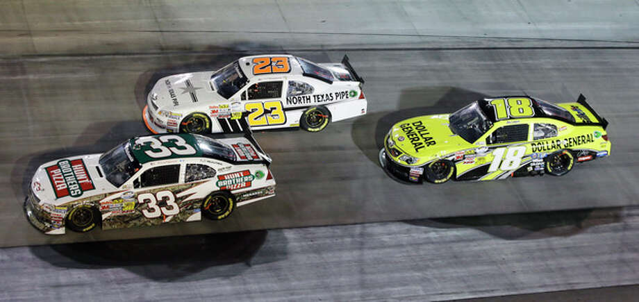 Joey Logano (18) follows Robert Richardson Jr. (23) and Kevin Harvick (33) through a turn during the Food City 250 NASCAR Nationwide Series auto race on Friday, Aug. 24, 2012, in Bristol, Tenn. Logano won the race. (AP Photo/Mark Humphrey) / AP