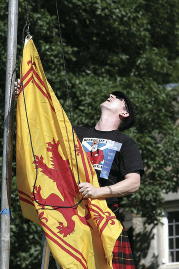 """Hour photo / David EspositoBruce Kennedy of Stamford raises the Flag of Scotland which features the """"Lion Rampant"""" at the 84th annual Round Hill Highland Games Saturday at Cranbury Park."""