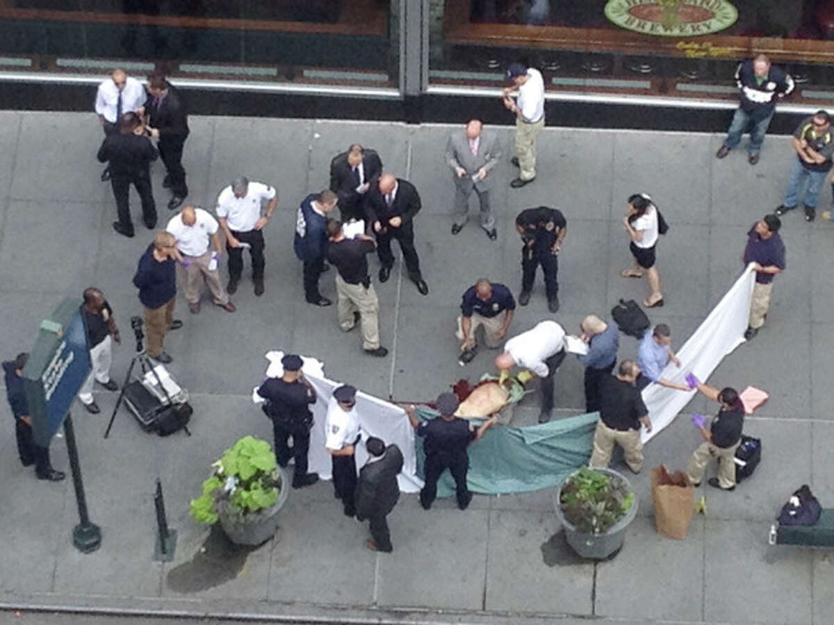 In this photo made with a cell phone, officials examine the body of gunman Jeffrey Johnson, who was killed by police gunfire after he fatally shot Steven Ercolino, an executive at his former company, outside the Empire State Building, Friday, Aug. 24, 2012, in New York. At least nine bystanders were hit by gunfire in the confrontation. (AP Photo/Lee Weinstein)